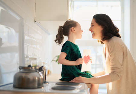 Happy mother's day! Child daughter is congratulating mom and giving her postcard. Mum and girl smiling and hugging. Family holiday and togetherness.