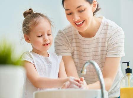 Śliczna mała dziewczynka i jej matka myją ręce. Zdjęcie Seryjne
