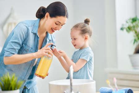 Śliczna mała dziewczynka i jej matka myją ręce.