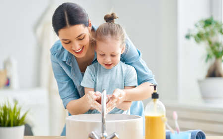 A cute little girl and her mother are washing their hands. Фото со стока