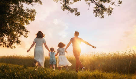 Happy family on summer walk! Mother, father and daughters walking in the Park and enjoying the beautiful nature. Foto de archivo