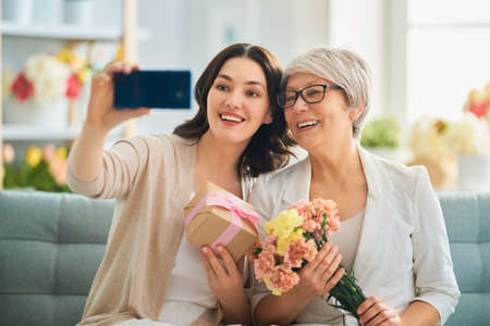 Happy mothers day! Beautiful young woman and her mother with flowers and gift box at home.