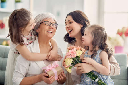 Children daughters are congratulating mom and granny giving them flowers and gift. Grandma, mum and girls smiling and hugging. Family holiday and togetherness. Stockfoto