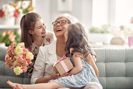 Children daughters are congratulating granny giving her flowers and gift. Grandma and girls smiling and hugging. Family holiday and togetherness.