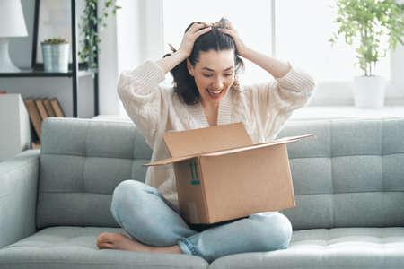 Beautiful young woman is holding cardboard box sitting on sofa at home. Фото со стока