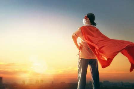 Arzt, der während des Ausbruchs des Coronavirus Gesichtsmaske und Superhelden-Umhang trägt. Viren- und Krankheitsschutz, Quarantäne. COVID-2019. Superheldenkraft für die Medizin. Person auf Sonnenuntergangstadtbildhintergrund.