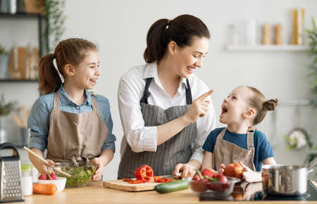 Healthy food at home. Happy family in the kitchen. Mother and children daughters are preparing vegetables. Reklamní fotografie