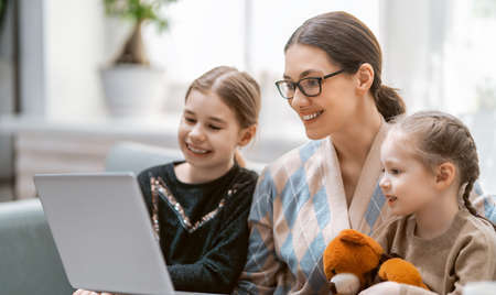 Happy loving family. Young mother and daughters girls using laptop. Funny mom and lovely children are having fun staying at home.