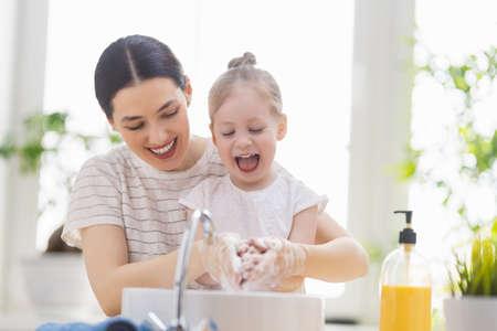 Una niña linda y su madre se lavan las manos. Protección contra infecciones y virus.