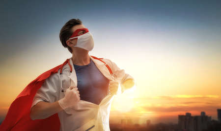 Doctor wearing facemask and superhero cape during coronavirus outbreak. Virus and illness protection, quarantine. COVID-2019. Super hero power for medicine. Person on sunset cityscape background. Reklamní fotografie