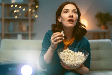 Young woman watching movies with popcorn in the evening.