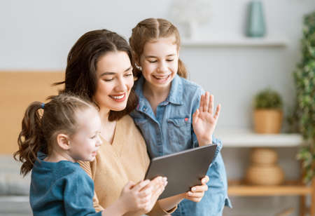 Happy loving family. Young mother and daughters girls using tablet pc for remote conversation with friends. Funny mom and lovely children are having fun staying at home.