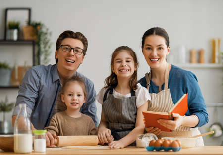 Happy loving family are preparing bakery together. Father, mother and children daughters girls are cooking cookies and having fun in the kitchen. Homemade food and little helper. Banque d'images