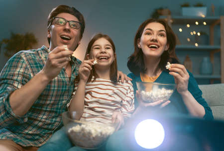 Happy family watching projector, TV, movies with popcorn in the evening at home. Mother, father and daughter spending time together. Banque d'images