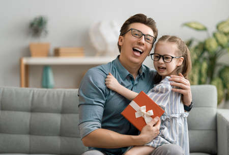 Happy father's day! Child daughter congratulating dad and giving him gift box. Daddy and girl smiling. Family holiday and togetherness. Banque d'images