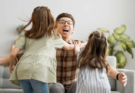Happy loving family. Daddy and his daughters children girls playing together. Father's day concept. Banque d'images