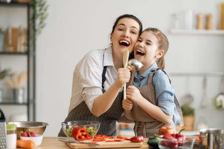 Comida sana en casa. Familia feliz en la cocina. La madre y la hija del niño están preparando una comida adecuada.