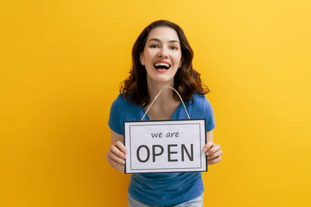 Small business owner smiling and holding the sign for the reopening of the place after the quarantine. Stock Photo
