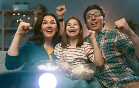 Happy family watching projector, TV, movies with popcorn in the evening at home. Mother, father and daughter spending time together. 版權商用圖片