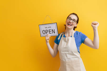 Small business owner smiling and holding the sign for the reopening of the place after the quarantine Stock Photo