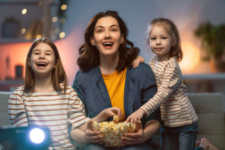 Happy family watching projector, TV, movies with popcorn in the evening at home. Mother and daughters spending time together.