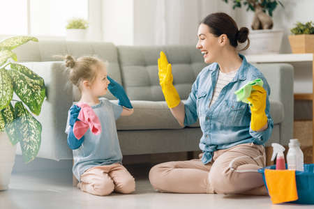Happy family at home. Mother and daughter doing the cleaning in the house. A young woman and child girl are dusting. Cute little helper.