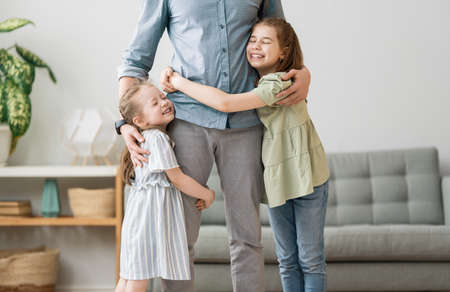 Happy loving family. Daddy and his daughters children girls playing together. Father's day concept. 版權商用圖片