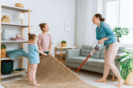 Happy family vacuuming the room. Mother and daughters doing the cleaning in the house.