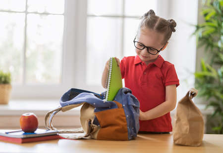 Happy child preparing for school. Little girl is putting things into backpack. Banque d'images