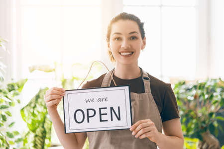 Small business owner smiling and holding the sign for the reopening of the place after the quarantine due to covid-19. Stock Photo