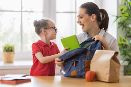 Happy family preparing for school. Little girl with mother putting things into backpack.