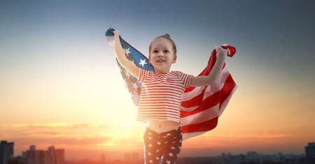Patriotic holiday. Happy kid, cute little child girl with American flag. USA celebrate 4th of July. Archivio Fotografico