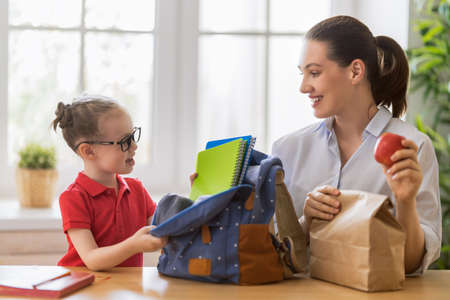 Happy family preparing for school. Little girl with mother putting things into backpack. Standard-Bild