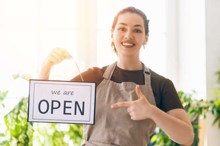 Small business owner smiling and holding the sign for the reopening of the place after the quarantine due to covid-19.