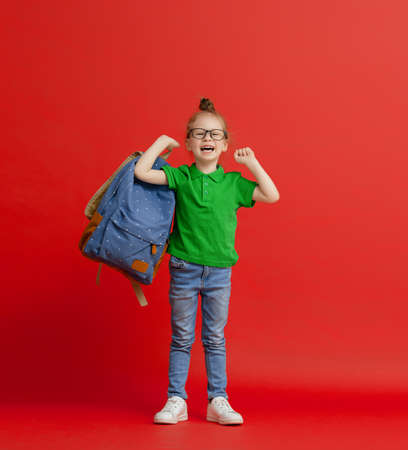 Back to school and happy time! Cute industrious child on color paper wall background. Kid with backpack. Girl ready to study. Stockfoto