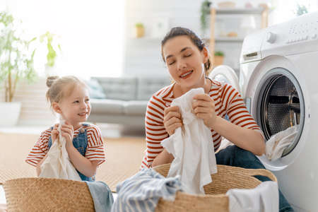 Beautiful young woman and child girl little helper are having fun and smiling while doing laundry at home. Reklamní fotografie