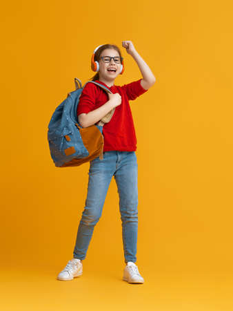 Back to school and happy time! Cute industrious child is jogging on color paper wall background. Kid with backpack. Girl ready to study. 免版税图像