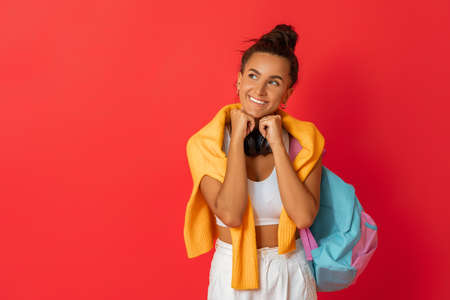 Happy emotional young woman in sporty clothes laughing on bright red background