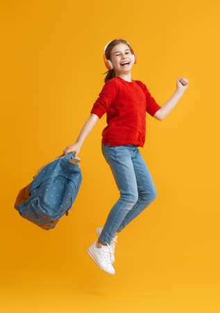 Back to school and happy time! Cute industrious child is jogging on color paper wall background. Kid with backpack. Girl ready to study. Foto de archivo