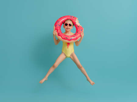 Happy child wearing swimsuit. Girl with swimming ring donut. Kid on a colored turquoise background.