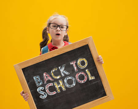 Back to school and happy time! Cute industrious child on color paper wall background. Kid with backpack. Girl ready to study.