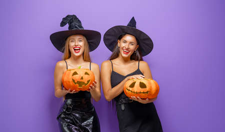 Happy Halloween! Two young women in black witch costumes with pumpkins on party on purple color background. Zdjęcie Seryjne