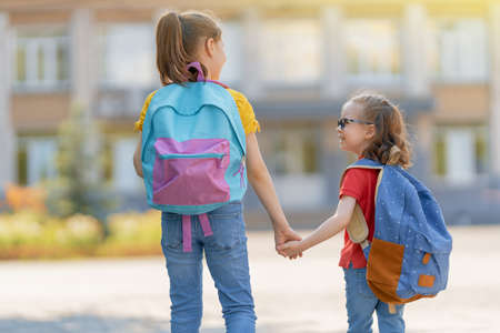 Pupils of primary school. Girls with backpacks outdoors. Beginning of lessons. First day of fall. 免版税图像