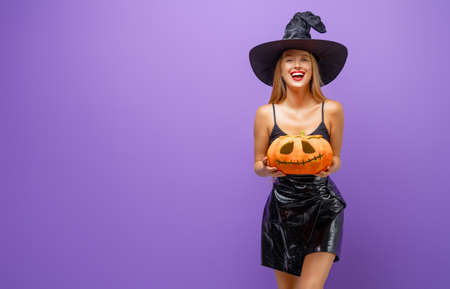 Happy Halloween! Young woman in black witch costume with pumpkin on party on purple color background.
