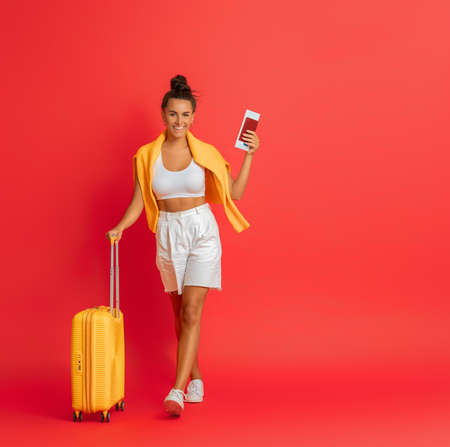 Go on an adventure! Happy woman going traveling. Young person with suitcase on color background.