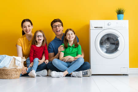 Man, woman and children girls little helpers are having fun and smiling while doing laundry at home. 免版税图像