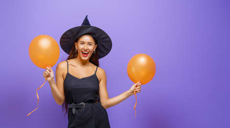 Happy Halloween! Young woman in black witch costume with air balloons on party on purple color background.