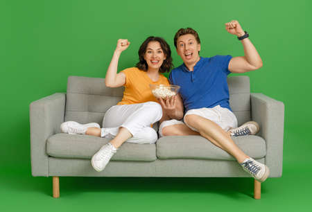 Young couple sports fans with popcorn sitting on the sofa on bright color background.