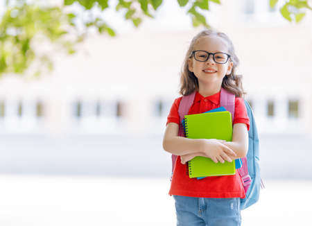 Pupil of primary school with book in hand. Girl with backpack near building outdoors. Beginning of lessons. First day of fall. 免版税图像