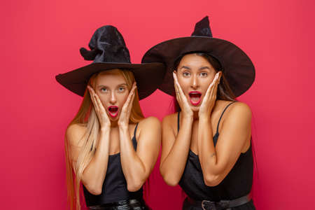 Happy Halloween! Two young women in black witch costumes on party on red color background.
